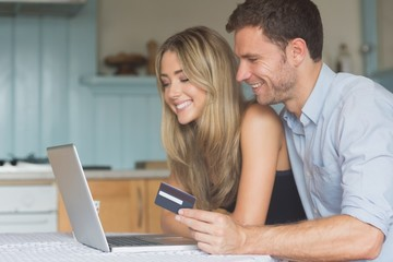 Cute couple using laptop together to shop online