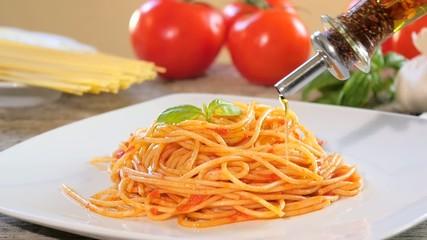 pouring olive oil over spaghetti