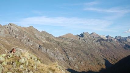 Woman reaches mountain summit, looks at stunnig view