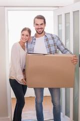 Cute couple carrying cardboard box