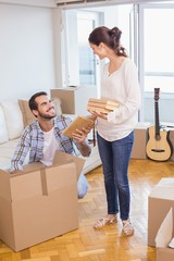 Cute couple unpacking cardboard boxes