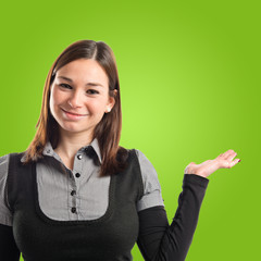 Young pretty woman holding something over green background