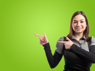 Young pretty woman pointing over green background