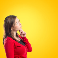 woman thinking over yellow background