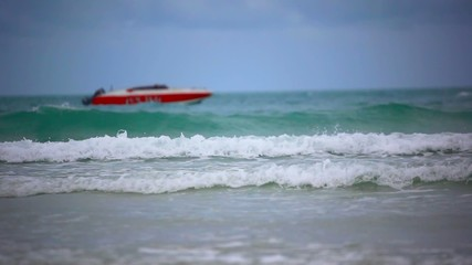 Red boat on a beach. Sea waves during cloudy weather. HD.