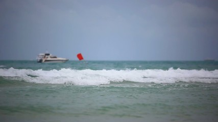 Sea waves during cloudy weather. Red flag for which you can not