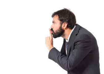 Businessman making silence gesture over isolated white backgroun
