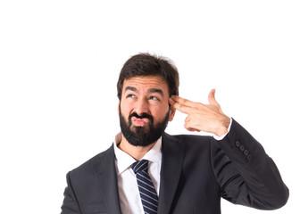 Businessman making gun gesture over white background
