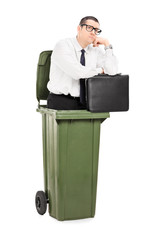 Pensive businessman standing inside a trash can