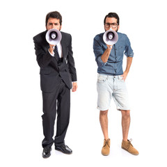Brothers shouting by megaphone over white background