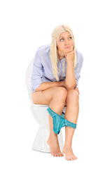 Pensive young woman sitting on a toilet and thinking