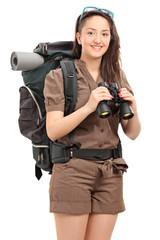 Vertical shot of a female hiker holding binoculars