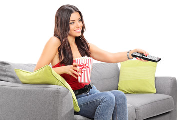 Young woman watching TV seated on a sofa