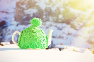 Tea pot in the knitted cap on the snow