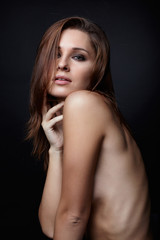 Young topless woman on black