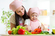 Mother teaches daughter on kitchen