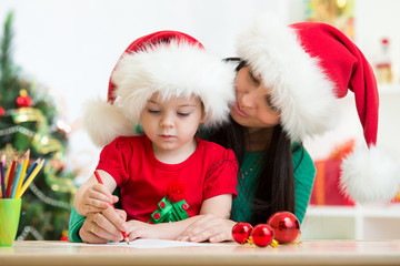 Child girl and mom writing christmas letter to Santa