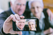 canvas print picture - Senior couple showing self portrait photo on smartphone