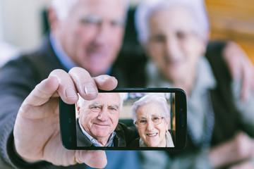 Senior couple showing self portrait photo on smartphone