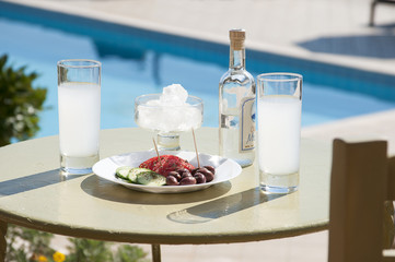 Ouzo and tasters in front of swimming pool.
