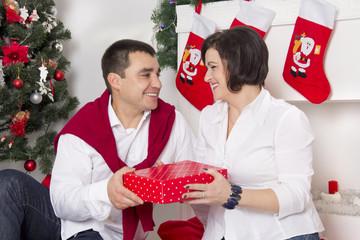 couple sitting near the Christmas fireplace
