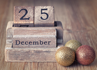Old vintage wooden calendar set on the 25 of December  with chri