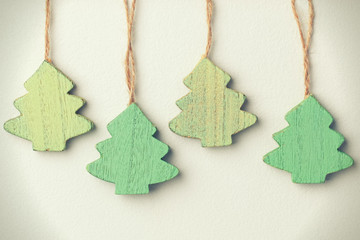 Green vintage wooden christmas trees hanging on a string