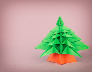 Origami christmas tree on pink background