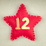 Red star with wooden number 12 on vintage fabric background