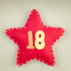 Red star with wooden number 18 on vintage fabric background
