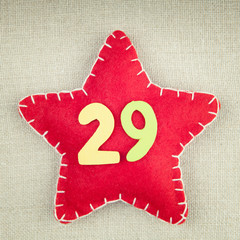 Red star with wooden number 29 on vintage fabric background