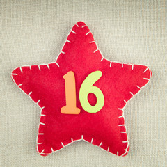 Red star with wooden number 16 on vintage fabric background