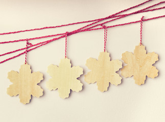 Handmade wooden snowflakes hanging on red strings