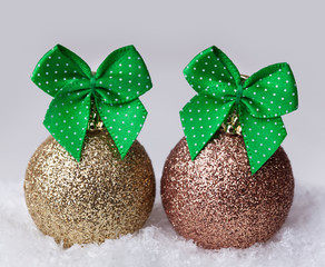 Christmas balls with green bow in the snow