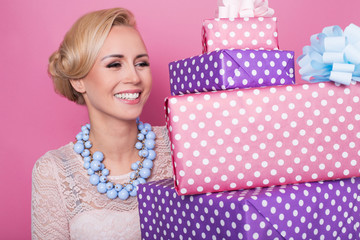 Woman with big beautiful smile holding colorful gift boxes