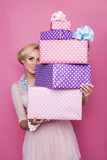 Fototapety Beautiful blonde woman looking through colorful gift boxes
