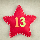 Red star with wooden number 13 on vintage fabric background