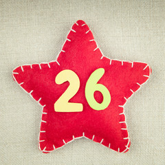 Red star with wooden number 26 on vintage fabric background
