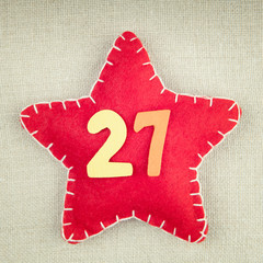 Red star with wooden number 27 on vintage fabric background