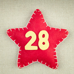 Red star with wooden number 28 on vintage fabric background