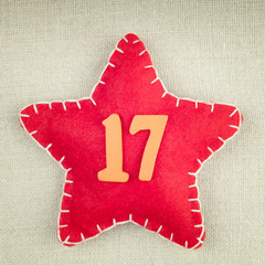 Red star with wooden number 17 on vintage fabric background
