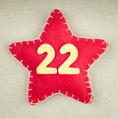 Red star with wooden number 22 on vintage fabric background