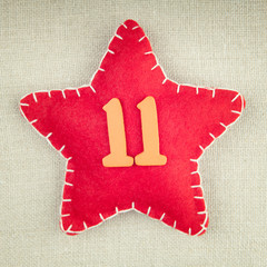 Red star with wooden number 11 on vintage fabric background