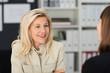 zwei lächelnde frauen im büro unterhalten sich