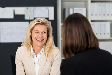 zwei frauen unterhalten sich im büro