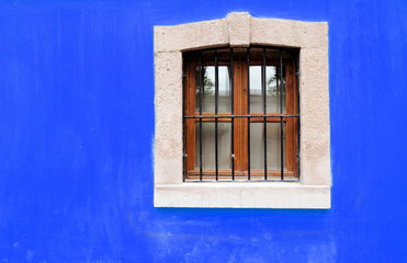 Stone window on Blue wall background house fasade