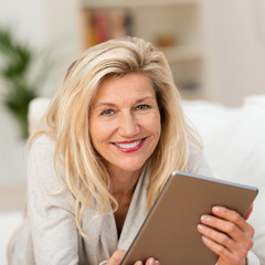 lächelnde best-ager frau mit ihrem tablet