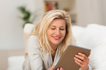 entspannte frau liest ein e-book auf dem sofa
