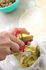 hands peeling potato with peeler