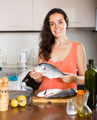 Woman holding fish at kitchen